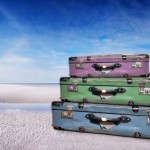 Photo of 3 suitcases on a beach depicting travel insurance