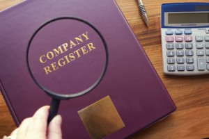 A photo of a Company Register under a magnifying glass
